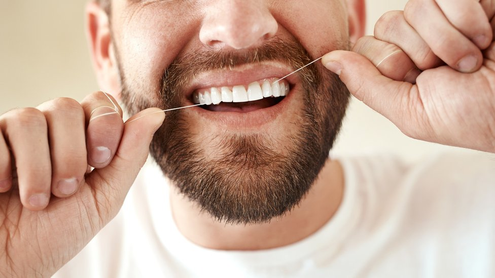 hombre con hilo dental