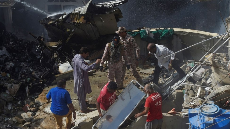 Rescue workers gather at the site after a Pakistan International Airlines flight crashed in a residential neighbourhood