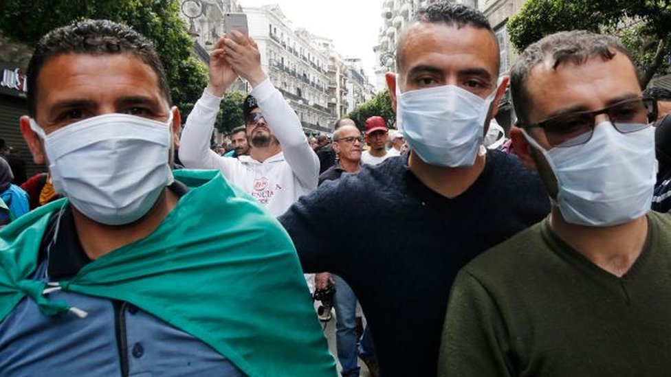 Protesting Algerians wearing mask