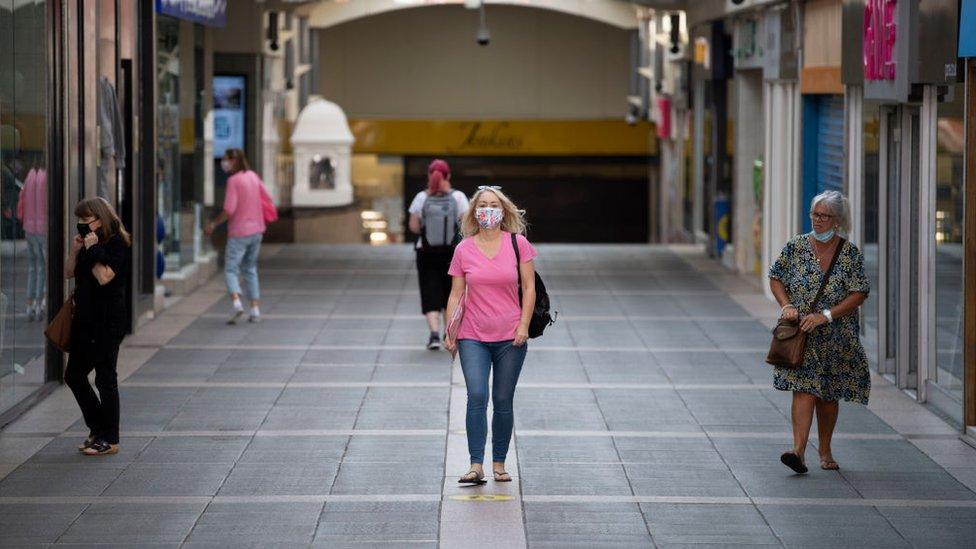 A woman walking through Bridgend wearing a face mask