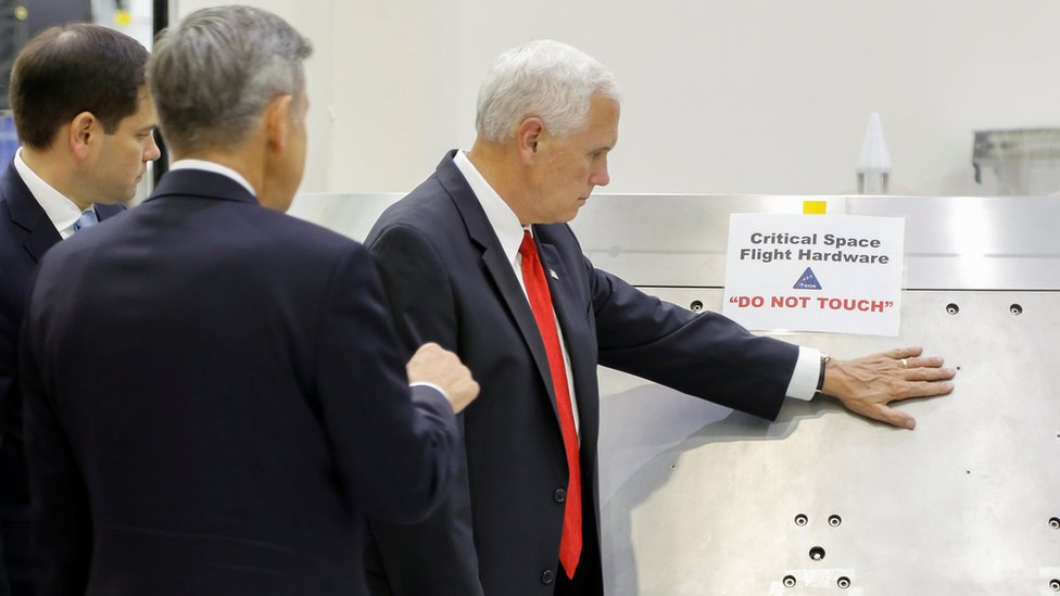 "US Vice-President Mike Pence touches a piece of hardware with a warning label ""Do Not Touch"" at the Kennedy Space Centre, 6 July 2017"