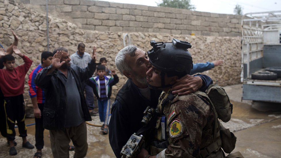 A man kisses an Iraqi special forces soldier in Mosul, 2 November 2016