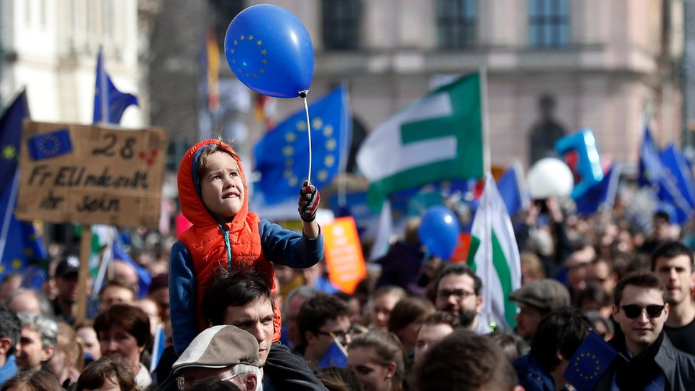 """A child holds a balloon with the European logo during the """"March for Europe"""" rally in Berlin, Germany, 25 March 201"""