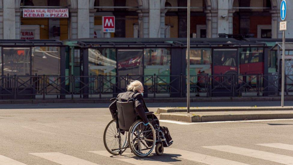 Un anciano cruza la calle en silla de ruedas.