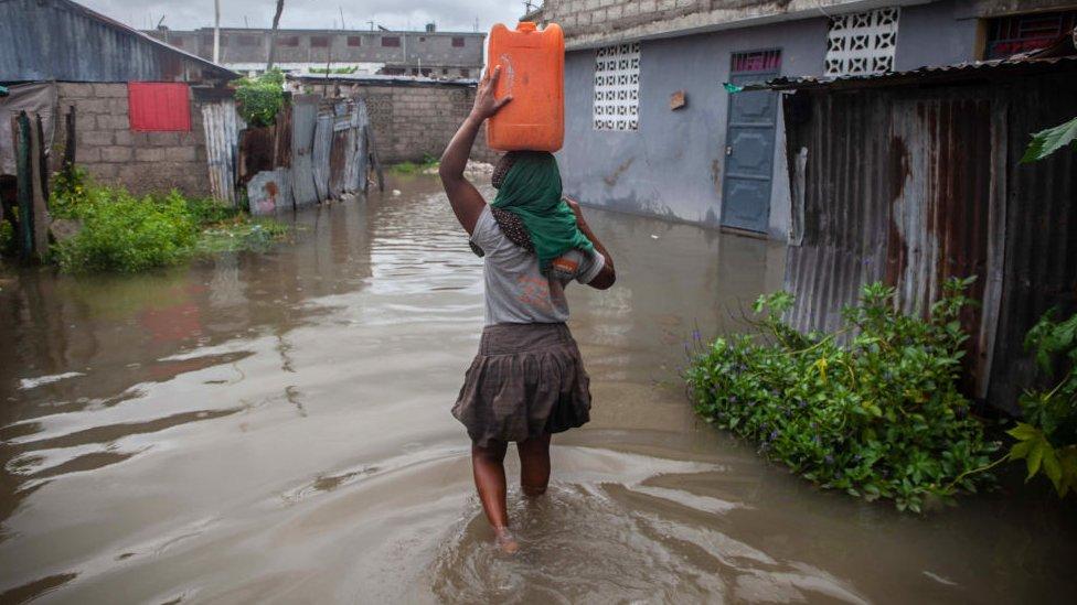 Una mujer intenta trasladarse por un terreno inundado.