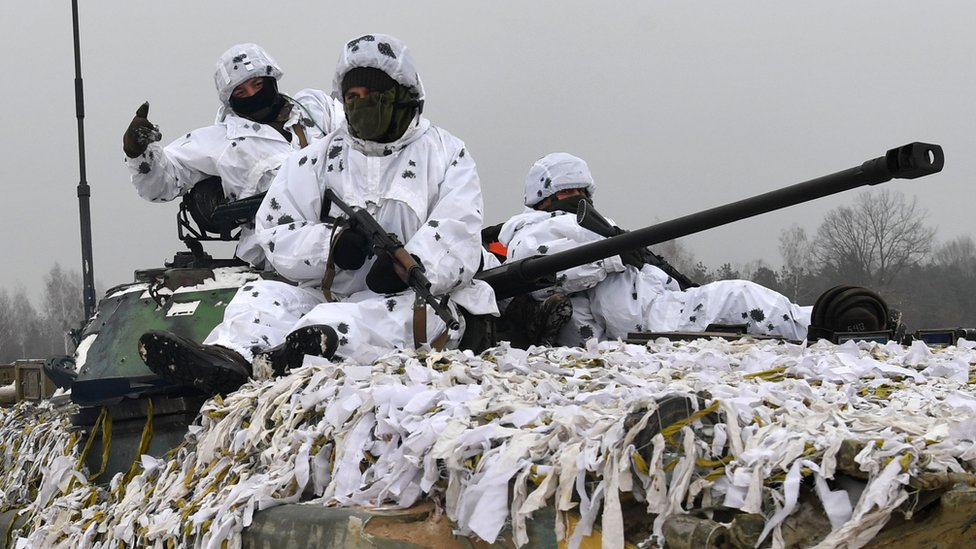 Three heavily armed Ukrainian servicemen clad in white camouflage site on top of a tank covered in similarly white fabric strips, with the tank's cannon protruding from the gap between the men