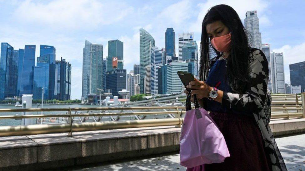امرأة تتفحص هاتفها المحمول أمام عدد من ناطحات السحاب