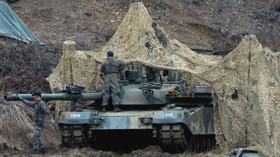 South Korean soldiers set up a camouflage net over their tank during a military exercise near the demilitarised zone separating the two Koreas in Paju, South Korea (07 March 2016)