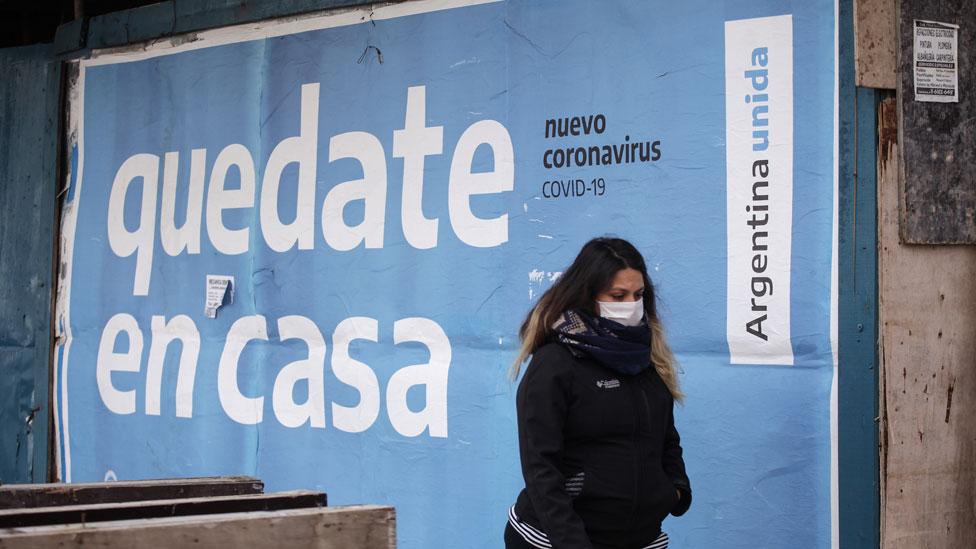 """Mulher com máscara passa em frente a cartaz que diz """"fique em casa"""" em espanhol"""
