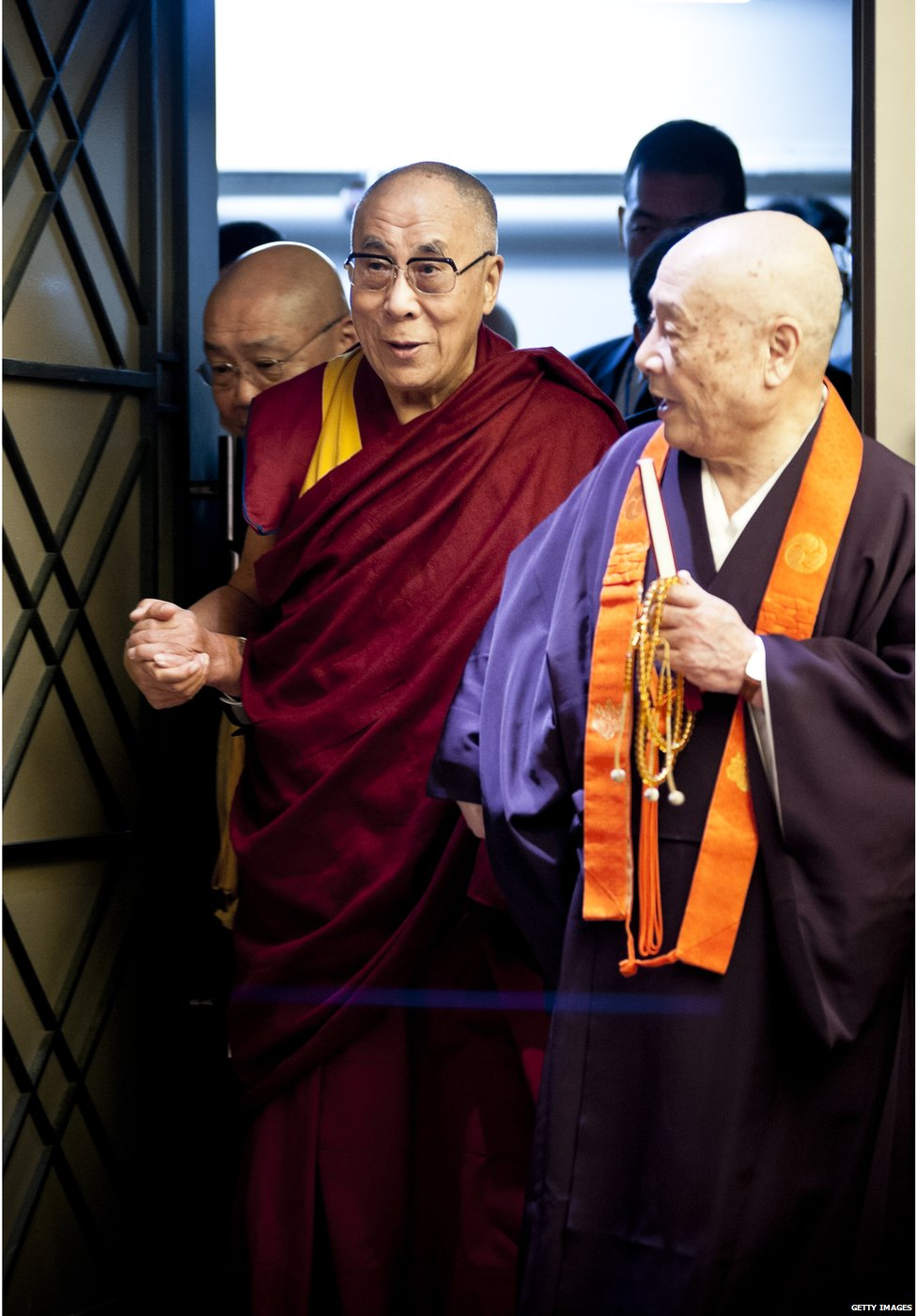 Tibetan spiritual leader the Dalai Lama (L) is introduced to guests during 'Dialogue in Tokyo' at Hotel Okura on 17 November 2013 in Tokyo, Japan