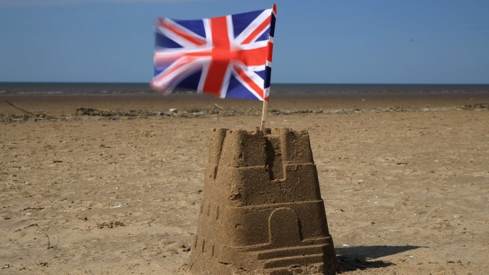 Sandcastle on Southwold beach with Union flag flying from the top