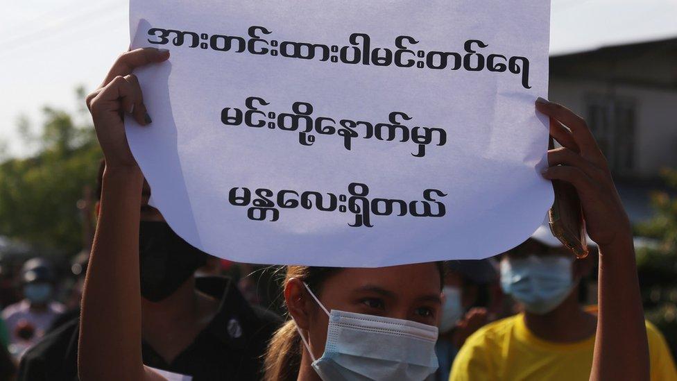 """Un joven muestra un cartel con el mensaje: """"Sé fuerte, Mindat""""."""