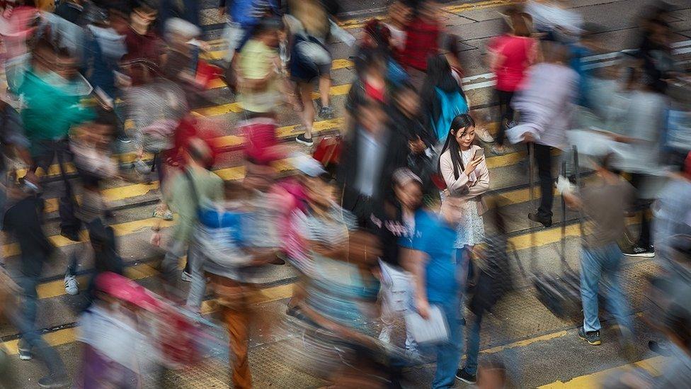Imagen con un tiempo de exposición largo con una mujer china parada en medio de un paso de peatones con mucha gente a su alrededor.