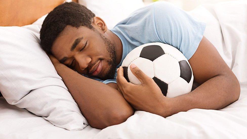 Un hombre duerme abrazado a un balón de fútbol.