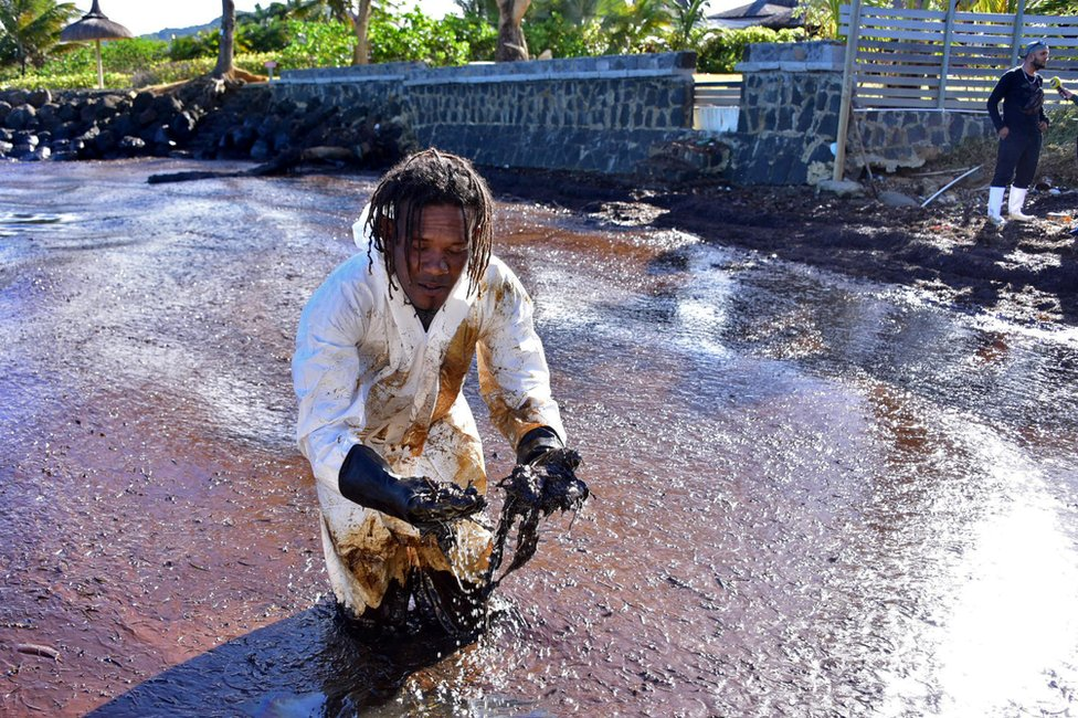 A volunteer stands in the sludge which he handles with gloved hands.