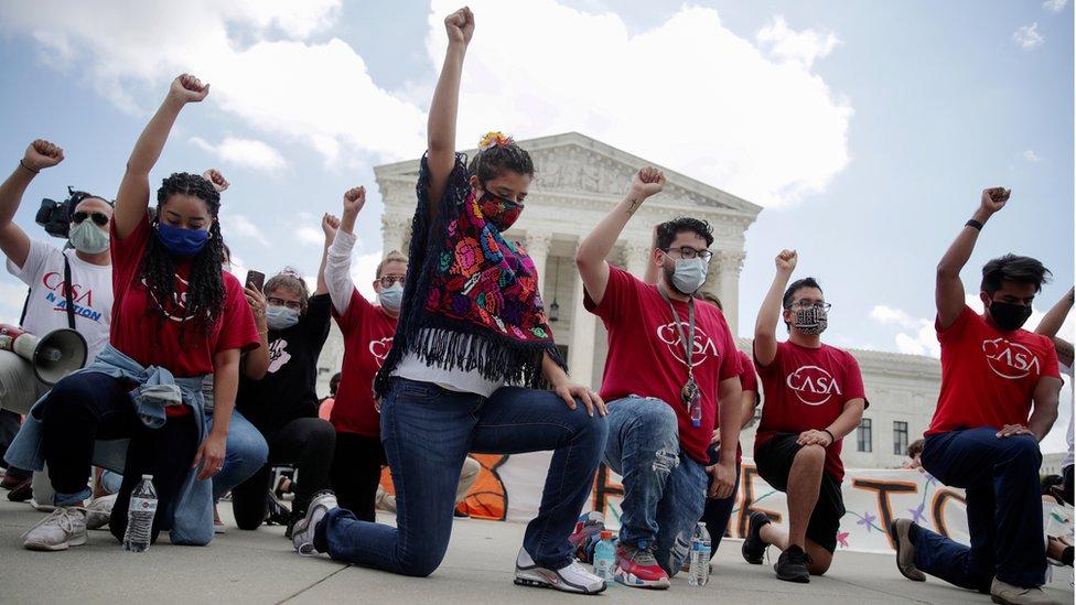 Grupo de hombres y mujeres arrodillados con el puño en alto ante la sede de la Corte Suprema de EE.UU.