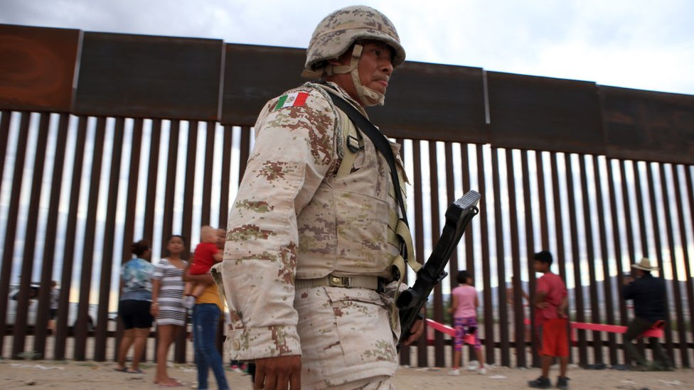 A Mexican soldier walks past children playing at the border