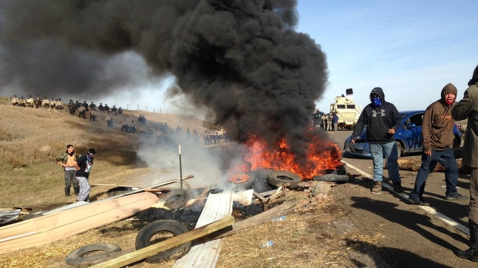 Dakota Access oil pipeline protesters burn debris as officers close in to force them from a camp on private land in the path of pipeline construction, Thursday, Oct. 27, 2016 near Cannon Ball, N.D.