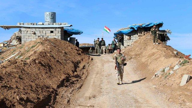 Kurdish peshmerga forces monitoring trenches they dug