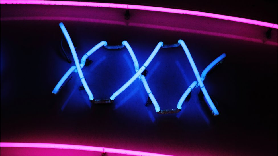 A stock image shows an XXX neon sign