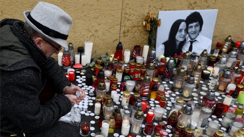 A man lights a candle for a tribute to murdered Slovak investigative reporter Jan Kuciak at Slovak National Uprising Square in Bratislava