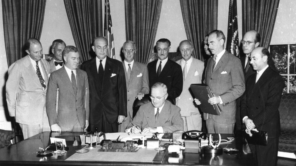 President Harry S. Truman signing the North Atlantic Treaty, marking the beginning of NATO, in 1949