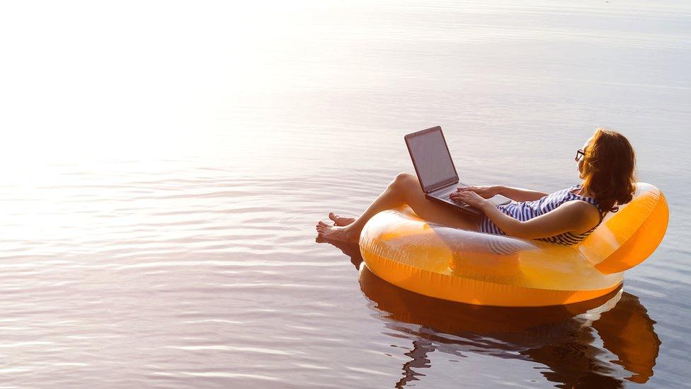 Mujer en un inflable con una computadora.