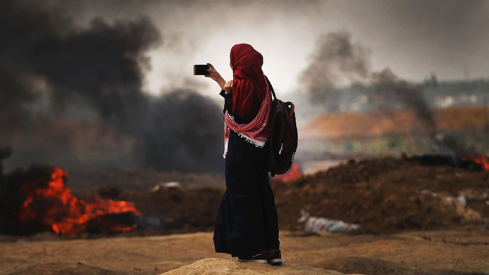 A Palestinian woman documents the situation at the border fence with Israel as mass demonstrations continue on May 14