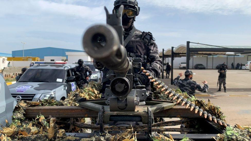 جندي على ظهر سيارة تحمل مدفعا رشاشا