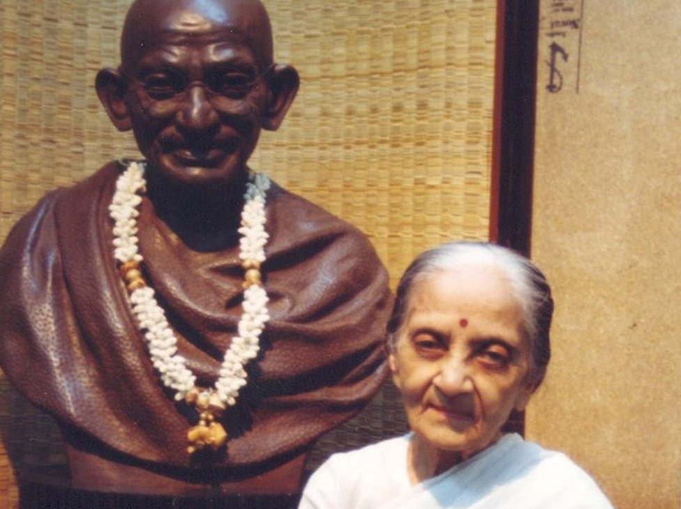 Usha Mehta standing next to a statue of Mahatma Gandhi