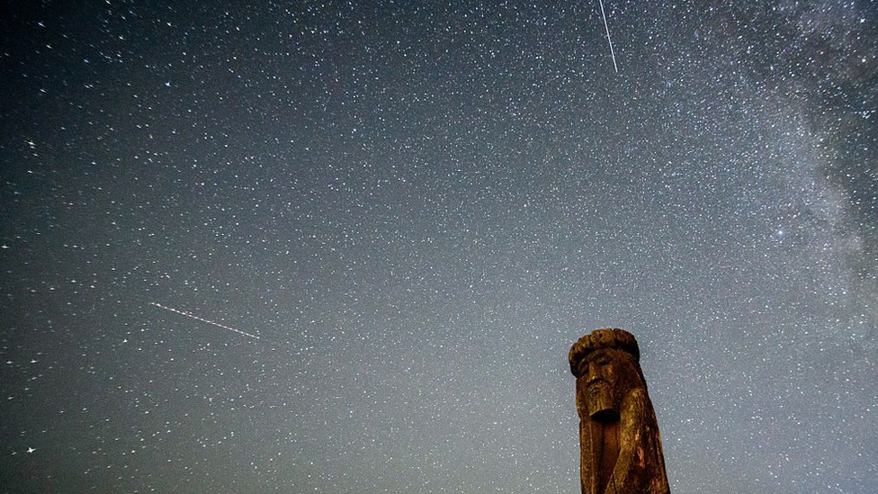Shooting stars cross the night sky over a wooden idol near the village of Ptich some 25km away from Minsk, during the peak of the annual Perseid meteor shower on 15 August 2015.