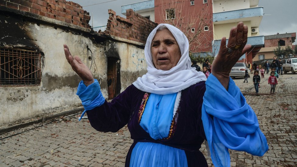 A woman outside her damaged house during fighting between government troops and separatist Kurdistan Workers' Party (PKK) fighters, in the Kurdish town of Silopi, in south-eastern Turkey