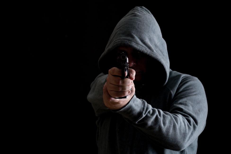 Un hombre encapuchado con un arma.