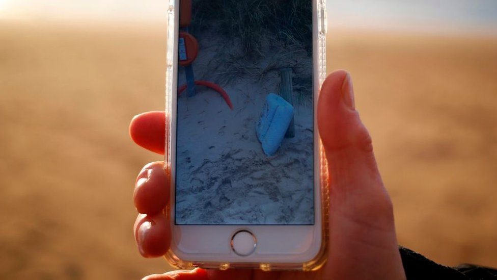 Celular mostrando la imagen de un cojín en la arena.