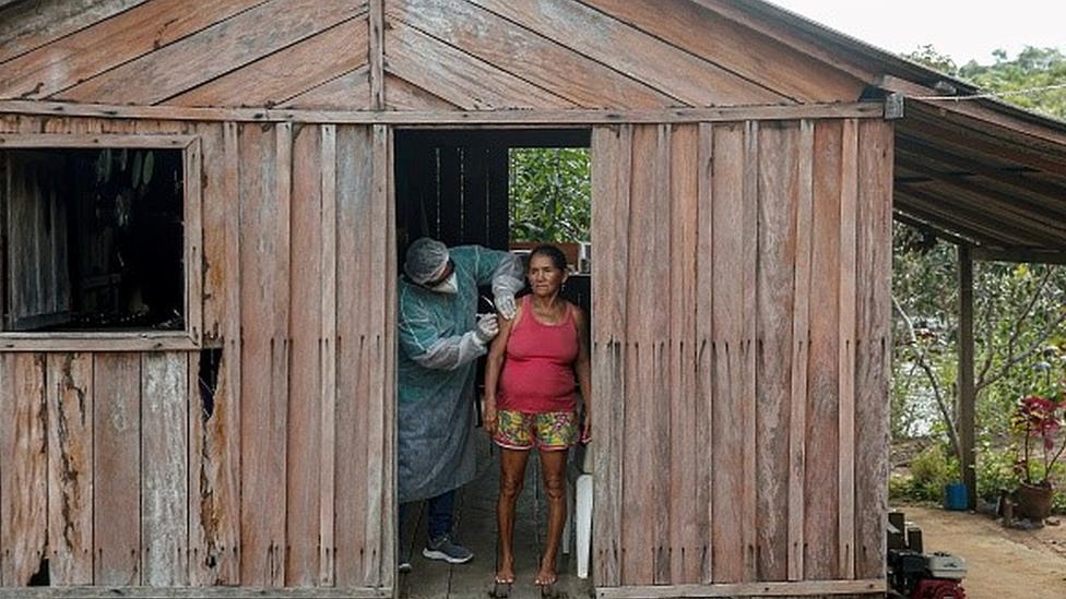 Mulher é vacinada em casa de madeira