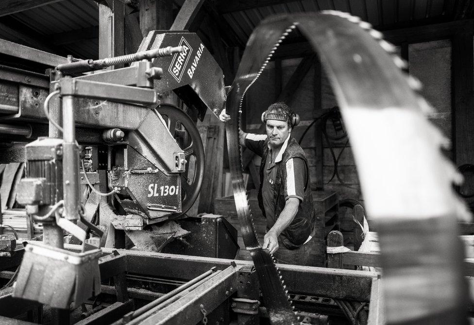 A man working on a saw machine
