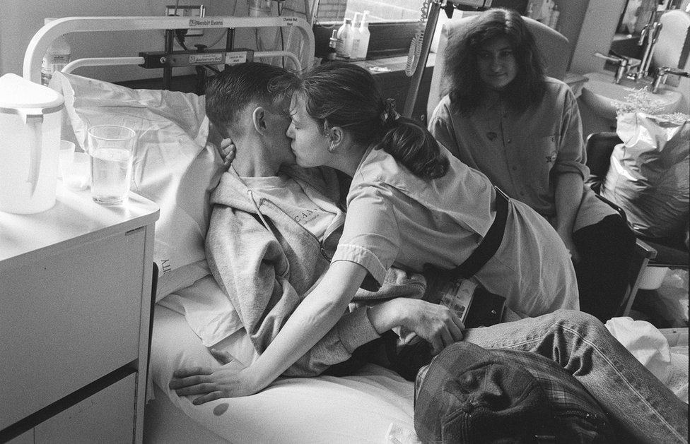 A nurse kisses a young patient.
