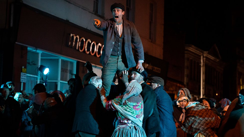 A scene from a Theatr Clwyd street production depicting the 1869 Mold Riots - a man held aloft, pointing and shouting