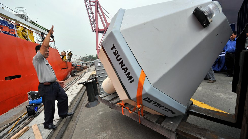Workers unload a Tsunami Buoy, a device to detect early tsunami warnings, in Jakarta