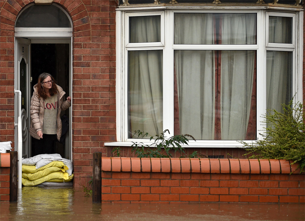 A woman stands with sandbags outside her house