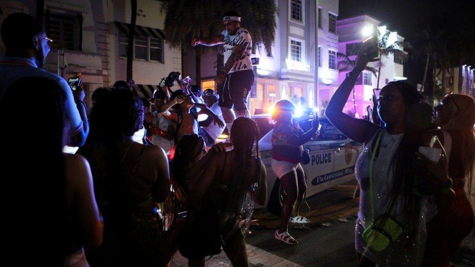 Un hombre baila arriba de un auto rodeado de una multitud en Miami Beach.