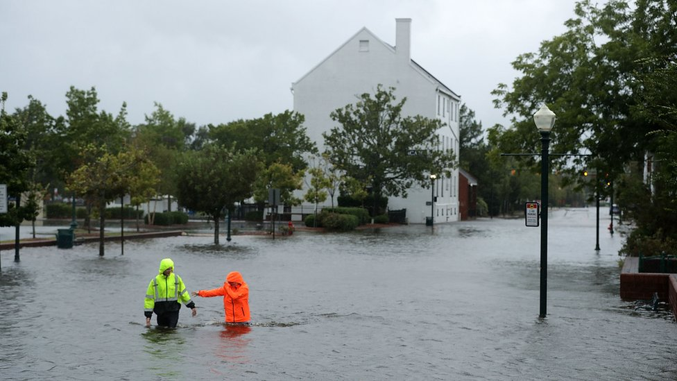 Residents walk in flooded streets as the Neuse River floods its banks during Hurricane Florence