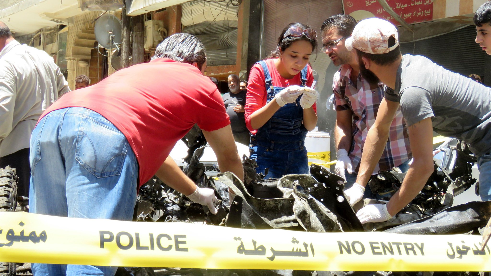 Syrian police check out the remains of a burnt-out car in Sayyida Zeinab on 11 June 2016