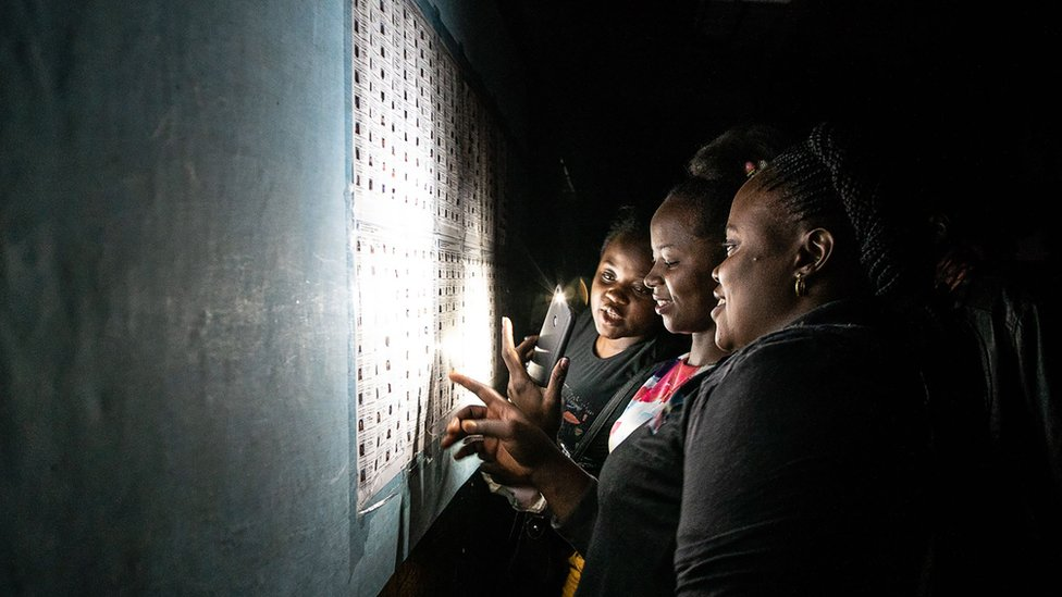 Late voters check a list after arriving at a polling station at Kiwele college in Lubumbashi on 30 December