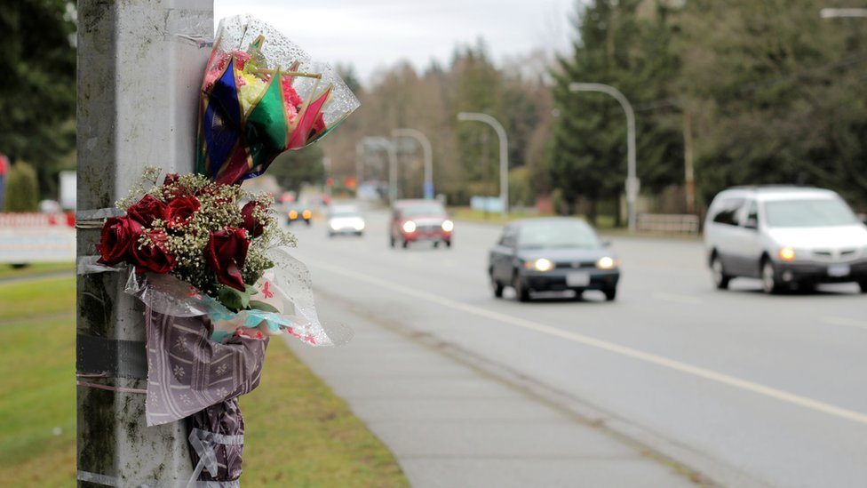 Flowers on lamppost marking scene of fatal accident