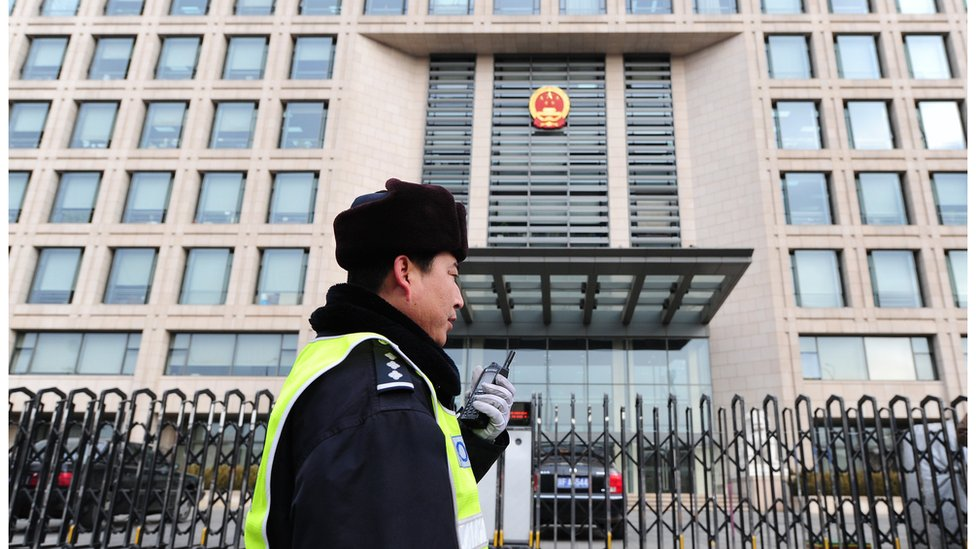 A policeman speaks into his walkie-talkie while on patrol outside the off-limits courthouse which upheld the 11-year jail term for leading Chinese dissident Liu Xiaobo. 11 Feb 2010, Beijing.