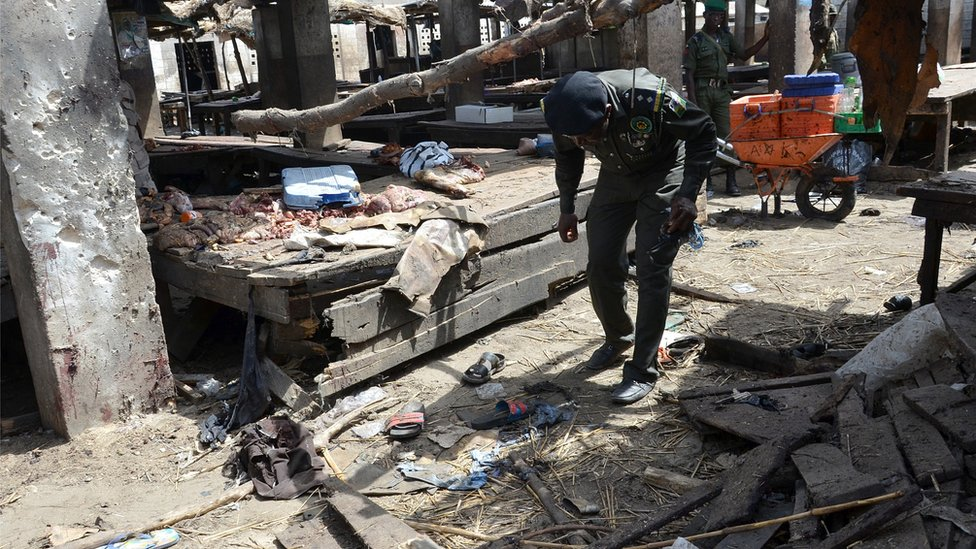 Nigerian policeman inspects the site of a suicide attack at a busy cattle market in the north-eastern Nigerian city of Maiduguri on June 2, 2015.