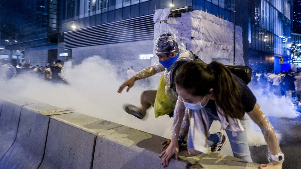 Pro-democracy activists run away during a demonstration in Hong Kong on September 28, 2014.