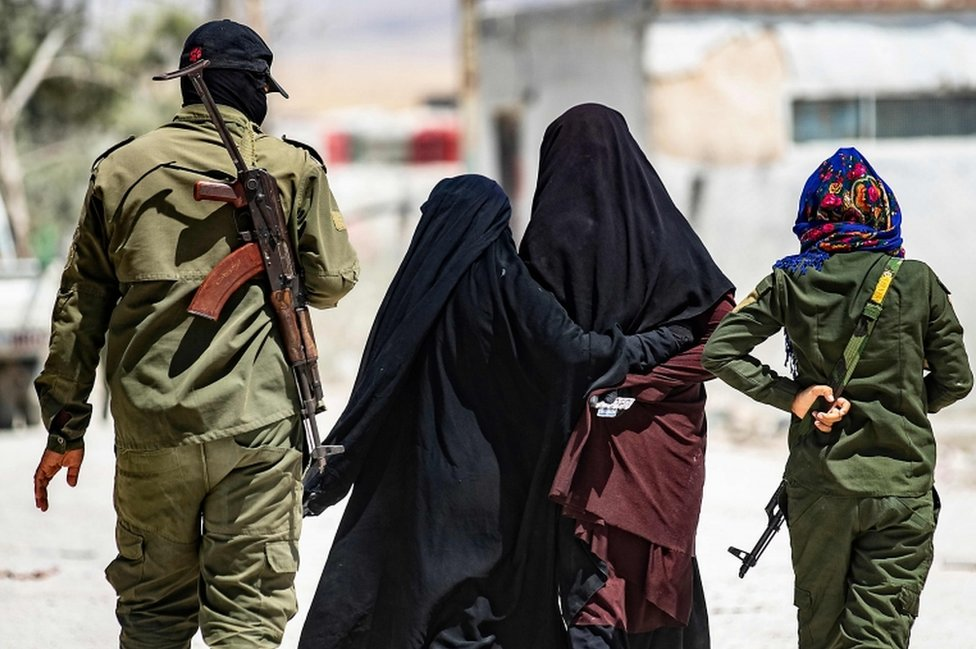 A security patrol escorts women, reportedly wives of Islamic State (IS) group fighters, in the al-Hol camp in north-eastern Syria