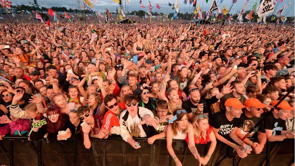 festivalgoers watch the Pyramid Stage at Glastonbury Festival. - 2017
